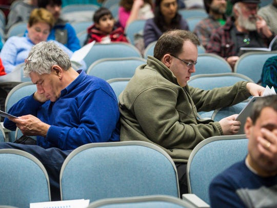Tom Joslin, left, and Ben Joslin peruse the town report during Jericho's town meeting at Mt. Mansfield Union High School on Tuesday, March 7, 2017.