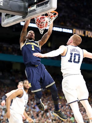 Michigan's Charles Matthews slams in front of Villanova's Donte DiVincenzo during the national championship game Monday, April 2, 2018, at the Alamodome in San Antonio.