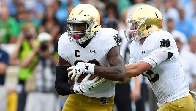Oct 7, 2017; Chapel Hill, NC, USA; Notre Dame Fighting Irish quarterback Ian Book (12) hands off to running back Josh Adams (33) in the first quarter at Kenan Memorial Stadium. Mandatory Credit: Bob Donnan-USA TODAY Sports
