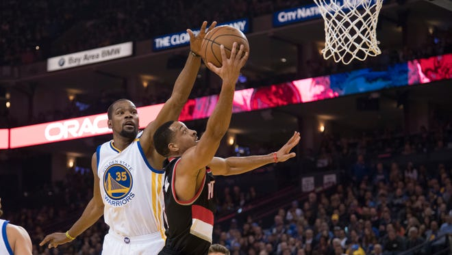 Portland Trail Blazers guard C.J. McCollum (3) shoots the basketball against Golden State Warriors forward Kevin Durant (35) during the first quarter at Oracle Arena.
