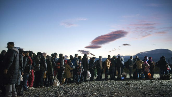 Migrants and refugees queue to enter a registration camp after crossing the Greek-Macedonian border near Gevgelija on November 8, 2015. The flow of refugees and other migrants from Turkey to Greece is expected to continue at a rate of 5,000 daily this winter, the UN refugee agency UNHCR said.
