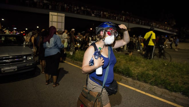 A protestor wearing a mask and goggles walks early July 10, 2016, on shut down Interstate 94 in St. Paul, Minn.