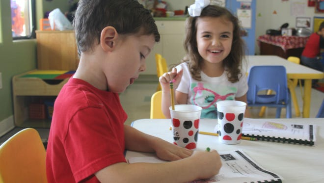 Children color at a local childcare facility.