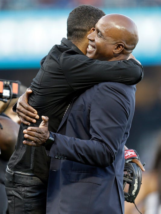 Former San Francisco Giants baseball player Barry Bonds, right, embraces his son Nikolai after throwing out a ceremonial first pitch prior to a baseball game against the Miami Marlins, Saturday, July 8, 2017, in San Francisco. (AP Photo/Ben Margot)