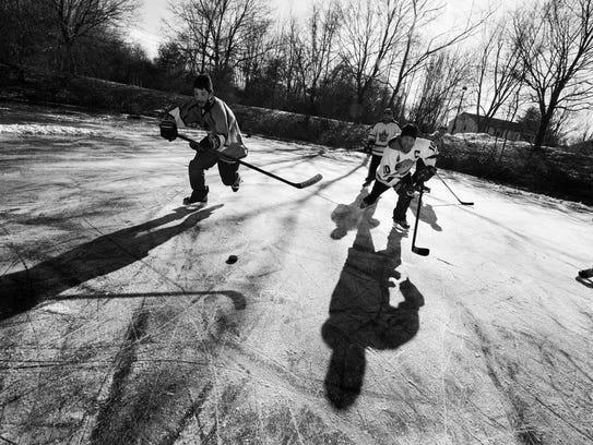 A photo by Nicholas Wynia shows a game of pond hockey.