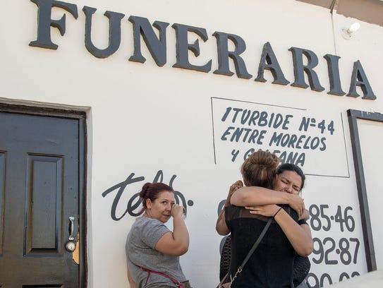Selene Ramirez (right) consoles her sister, Reyna Martinez,