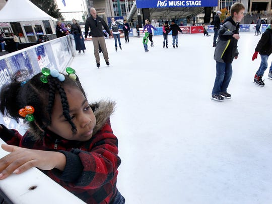 November 23, 2011: Jaymere Hutchinson, 5, of Price Hill, holds onto the wall while ice skating for the first time ever, on opening day of the Ice Rink on Fountain Square.