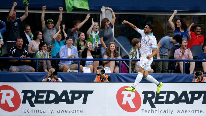 Seattle Sounders' Cristian Roldan leaps in celebration in front of fans after he scored a goal against the Portland Timbers in the first half of an MLS soccer match, Sunday, Aug. 27, 2017, in Seattle. (AP Photo/Ted S. Warren)