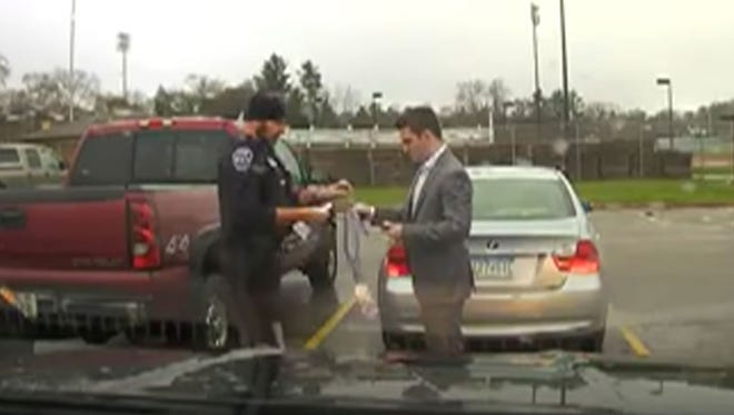 Dashcam video shows Menomonie, Wis., Officer Martin Folczyk giving the necktie back to the student to slip around his neck and tighten. The student had been stopped for speeding Nov. 30, 2016, but the officer gave him a warning and help tying his tie.