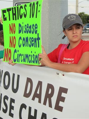 In this Jan. 10, 2015 photo, Jennifer Blanchard, 34, of Miami, protests in Boynton Beach, Fla., over the case of a little boy whose parents have been fighting over whether to circumcise him. Judges have ruled in favor of the boy's father, who wants his son to undergo the procedure. (AP Photo/Matt Sedensky)