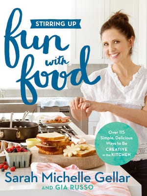"""This cover image released by Grand Central Life & Style shows """"Stirring Up Fun with Food: Over 115 Simple, Delicious Ways to Be Creative in the Kitchen,"""" by Sarah Michelle Gellar and Gia Russo."""