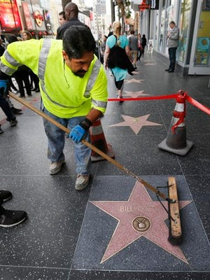 Eddy Giron cleans graffiti off the Bill Cosby star on the Hollywood Walk of Fame after it was defaced in Los Angeles on Friday, Dec. 5, 2014. The Hollywood Chamber of Commerce wrote in a statement that it hoped people upset with Cosby would find different ways to express themselves than vandalism. (AP Photo/Nick Ut)