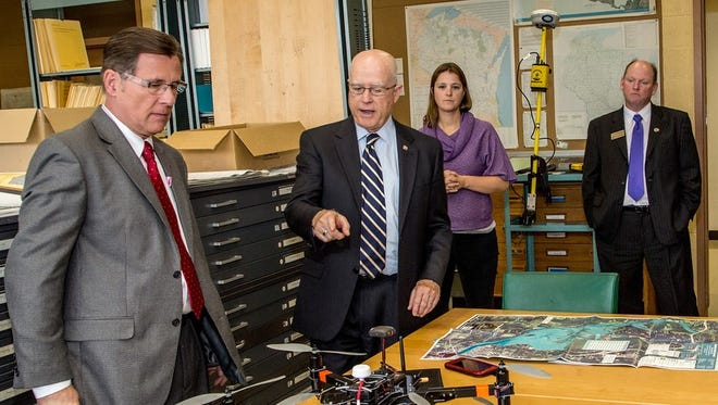 David Murphy, left, chair of the state Assembly Committee on Colleges and Universities, tours the Geographic Information Systems Center at UW-Stevens Point on Oct. 5. He was among several legislators and members of the UW Board of Regents to visit campus and learn more about programs and issues on campus. Here, Murphy and Chancellor Bernie Patterson check out an unmanned aerial vehicle for aerial data collection. It will be used in a new class offered in spring on unmanned aerial systems remote sensing operations.