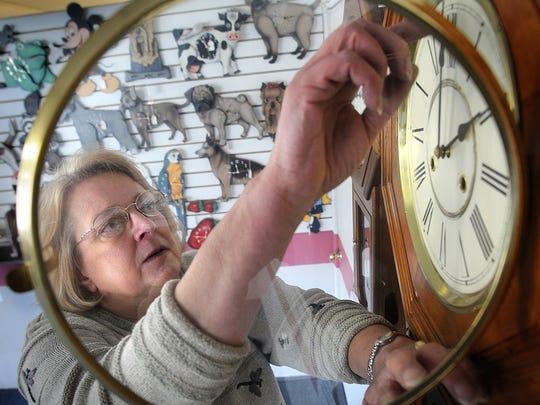 Kathy Faulls adjusts one of the many clocks at Pewaukee's