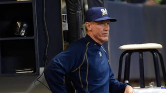 Ron Roenicke watches a game against the Cincinnati Reds.