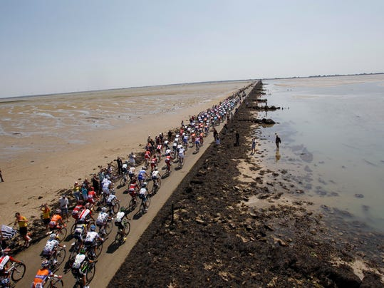 FILE - In this July 2, 2011 file photo, the pack passes the Passage du Gois, a causeway submerged by the tide twice a day joining Noirmoutier island and the mainland, rear, during the first stage of the Tour de France. Tour organizers unveiled Wednesday Feb. 28, 2017 the route for the three first stages of next year's edition of the race, which will start in the western Pays de La Loire region on June 30, 2018. Riders competing at the 2018 Tour de France will set off from the Passage du Gois. (AP Photo/Christophe Ena, File)