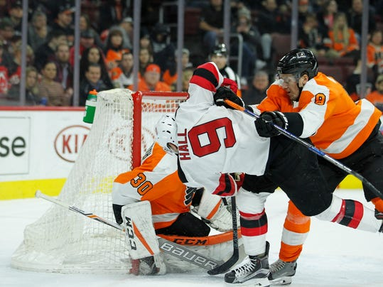 Philadelphia Flyers' Robert Hagg, right, clears New Jersey Devils' Taylor Hall from in front of the net defended by Michal Neuvirth during an NHL hockey game, Tuesday, Feb. 13, 2018 in Philadelphia. (AP Photo/Tom Mihalek)