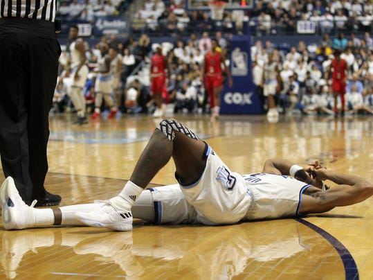 Rhode Island's E.C. Matthews (0) lies on the court after injuring his knee during the first half of an NCAA college basketball game against Richmond Tuesday, Feb. 13, 2018, in Kingston, R.I. (AP Photo/Stew Milne)