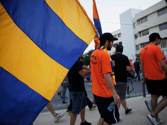 Fans of Cyprus soccer team APOEL hold flags of their team as they take part in a demonstration outside of the Cyprus Football Association in capital Nicosia, Cyprus, Tuesday, May 27, 2014. Hundreds of APOEL fans have staged a peaceful protest outside the Cyprus Football Association's headquarters over a decision to replay the season's abandoned final soccer match between the Nicosia team and rival AEL Limassol that would have decided the championship. (AP Photo/Petros Karadjias)