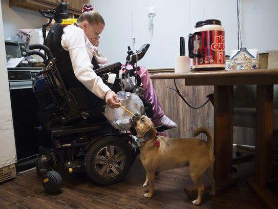 Sherri Kaspar hands her dog, Nala, a bone at her home