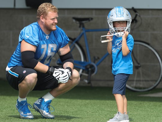 Lions guard T.J. Lang watches his son, J.J., 5, try