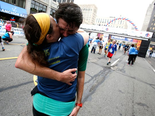Margaret Hanna gives a hug to her husband Paul Hanna, who was crying he crossed the finish line a with a marathon time of 4:13:43 during the 40th Detroit Free Press/Chemical Bank Marathon in Detroit on Sunday, Oct 15, 2017.