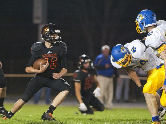Mishicot quarterback Morgan Meissner, left, carries the ball by himself during the first half of the game against Howards Grove Tigers on Friday in Mishicot. The Indians lost to the Tigers 15-12.