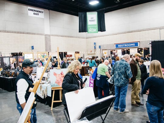 People attending a previous Dogwood Arts' House & Garden Show look at regional art in the show's Art Market section.