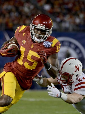 Wide Receiver Nelson Agholor of the USC Trojans runs away from Austin Williams of Nebraska in the National University Holiday Bowl Dec. 27, 2014.