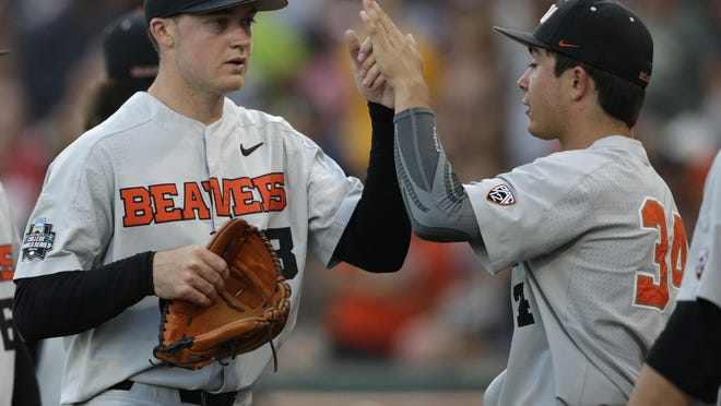 Oregon State pitcher Christian Chamberlain (right) greets teammate Kevin Abel following the seventh inning of Game 3 against Arkansas in the 2018 College World Series. Chamberlain was drafted in the fourth round of the MLB draft on Thursday by Kansas City.