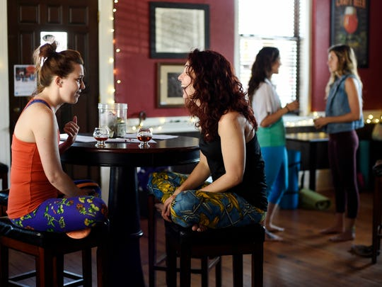 Kendra Gettys of York Township, left, and Desarae Ream of North York chat over beer samples after Speakeasy Yoga at Liquid Hero Brewery.