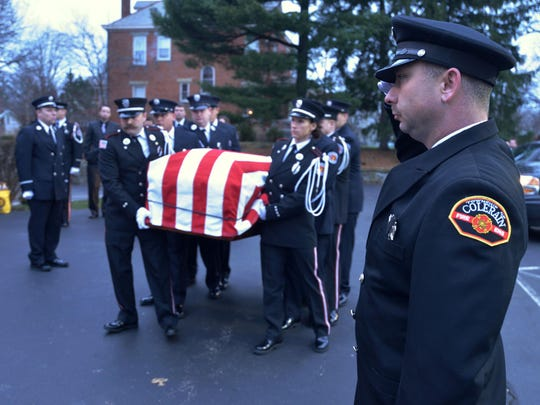 A Colerain firefighter salutes as the Hamilton Fire Color Guard carries the casket with fallen Hamilton Firefighter Patrick Wolterman during public services in 2015.