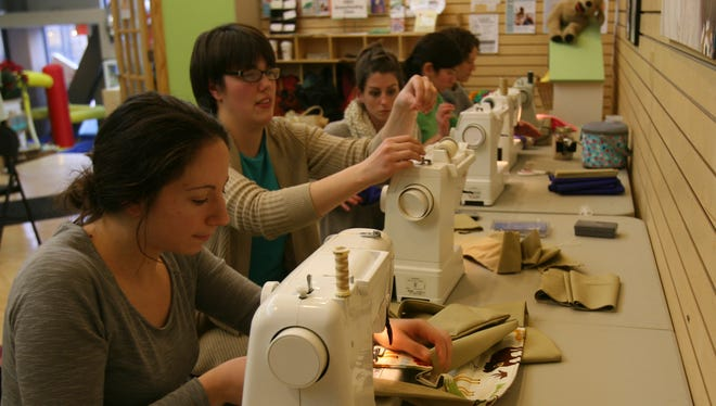 Lillian Shipman, second from left, organized a sew-in to make baby carriers for Kangaroo Care at a neo-natal intensive care unit in a small town in Nicaragua. Shipman, a nursing student at TC3, will deliver the carriers on Jan. 1. In the foreground is fellow nursing student Jennifer Tretter, of Ithaca.