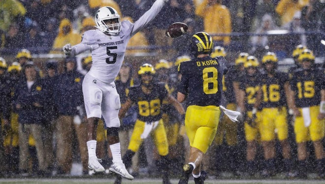 Michigan QB John O'Korn (8) throws as Michigan State LB Andrew Dowell (5) pressures during the second half of the game between MSU and U-M at Michigan Stadium in Ann Arbor on Sat., Oct. 7, 2017.