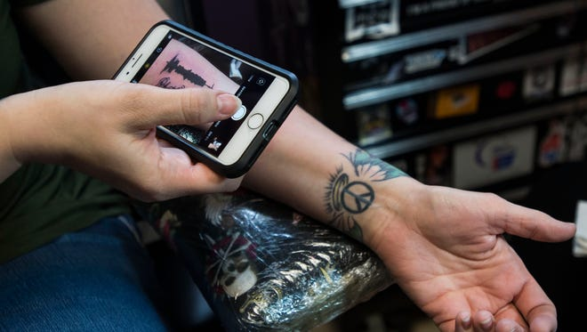 Natasha Dillenburg takes a photo of the skin motion tattoo being tattooed by Jen Wagner, an artist and owner of Genuine Tattoo, on Saturday, March 31, 2018, at Genuine Tattoo Parlor in Fort Collins, Colo.