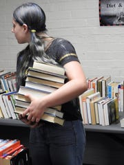 Kamryn Miller, 12, looks over at other books with her