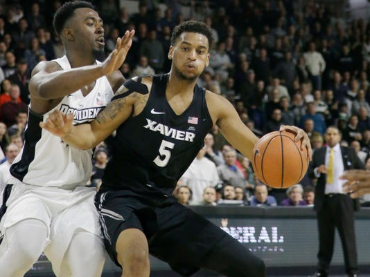 Providence guard Isaiah Jackson (44) applies defensive pressure as Xavier guard Trevon Bluiett (5) attempts to move to the hoop during the second half of their NCAA college basketball game Saturday, Jan. 6, 2018, in Providence, R.I. Providence upset No. 5 Xavier 81-72 . (AP Photo/Stephan Savoia)