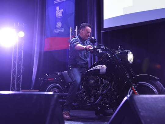 Bruce Springsteen arrives on stage on a motorcycle