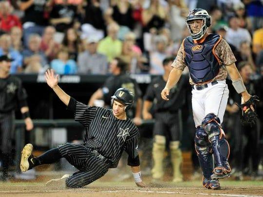 Vanderbilt's Bryan Reynolds scores a run past Virginia catcher Matt Thaiss during the sixth inning in the College World Series at TD Ameritrade Park, Monday, June 22, 2015, in Omaha, Neb.