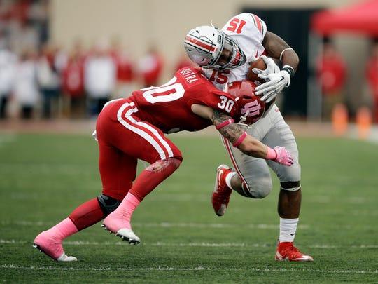 Ohio State's Ezekiel Elliott (15) is tackled by Indiana's Chase Dutra (30).