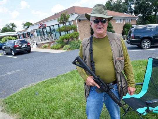 """Dave Beisner stands with his short barrel rifle as he keeps watch outside the Armed Forces Career Center on Richmond Road, a task he volunteered to do as a private citizen, in Staunton on Thursday, July 23, 2015. What we're doing here is providing protection for the recruiting officer until something more substantial is provided by either the Federal government or the state,"""" said Beisner. """"This is in the wake of Chattanooga, Tennessee, and other things.""""  He states he served seven years in the Army and 20 years with the FBI."""