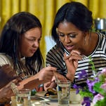 In this Tuesday, Oct. 14, 2014, file photo, first lady Michelle Obama and a student look over their plates as they eat lunch in the East Room of the White House following the annual fall harvest of the White House Kitchen Garden in Washington. To help address childhood obesity, the first lady made it her mission in 2014 to help push through tougher nutrition standards for food served in schools.
