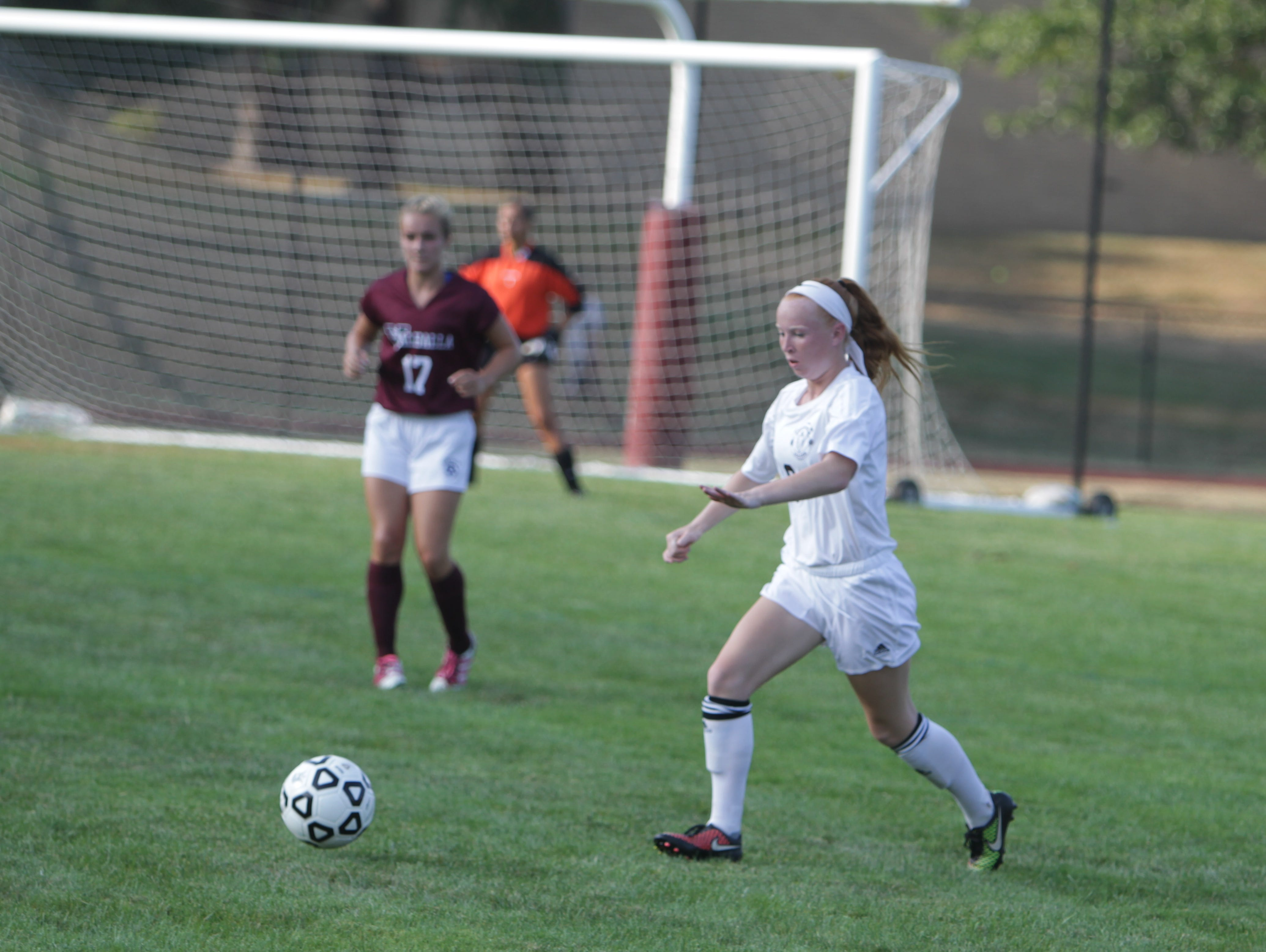 Albertus Magnus' Carly Clinton (white) controls the ball, with Valhalla's Kaylie Dymek (maroon) watching on, during a non-league game at Albertus Magnus High School on Tuesday, September 1st. Albertus Magnus won 1-0.