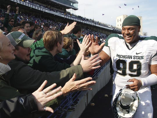 Michigan State's Jerel Worthy, right, celebrates with fans after they defeated Northwestern 35-27 in an NCAA college football game Saturday, Oct. 23, 2010 in Evanston, Ill. (AP Photo/Nam Y. Huh)