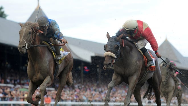 A crowd announced at 46,557 watched V.E. Day (outside) upset stablemate Wicked Strong in the 2014 Travers Stakes at Saratoga Race Course.