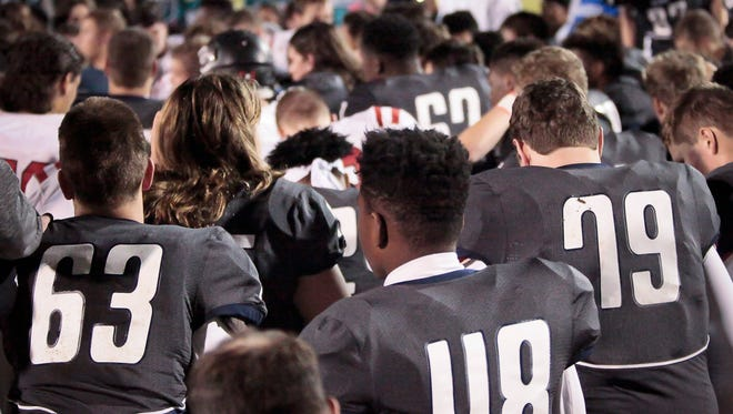 Players from both Siegel and Coffee County high schools as well as referees, cheerleaders, coaches and others gathered on the field of Friday night's game in Murfreesboro to pray for injured Siegel junior Baylor Bramble.