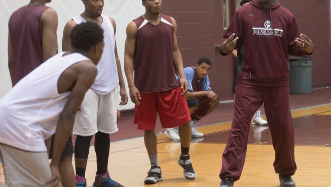 Pensacola High School Basketball Coach, Terrence Harris, right, walks his players through a play during practice for the upcoming Region 1-6A Semifinal game on Tueday night.
