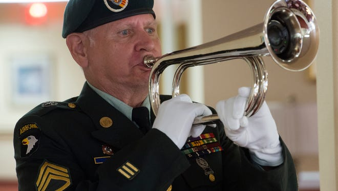 Earl Weekley symbolically plays taps in remembrance of fallen comrades during a Memorial Day tribute at University Pines Monday afternoon.