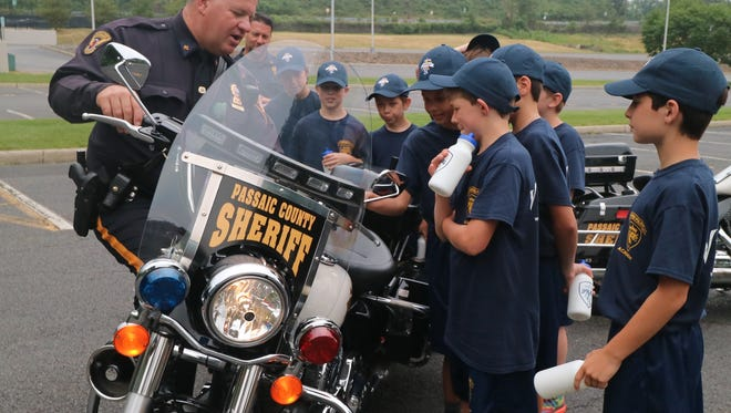 Wayne Junior Police Academy troopers admiring Officer Kaba's Harley-Davidson cruiser. The bike weighs 900 pounds and one of the first things a motorcycle officer must prove in training is that he or she can lift the bike off the ground.