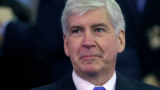 In this Feb. 11, 2015 file photo, Michigan Gov. Rick Snyder gets ready for an address in Lansing, Mich. Snyder used his extraordinary legal powers in December to pardon a politically connected lawyer who had a  drunken driving conviction.